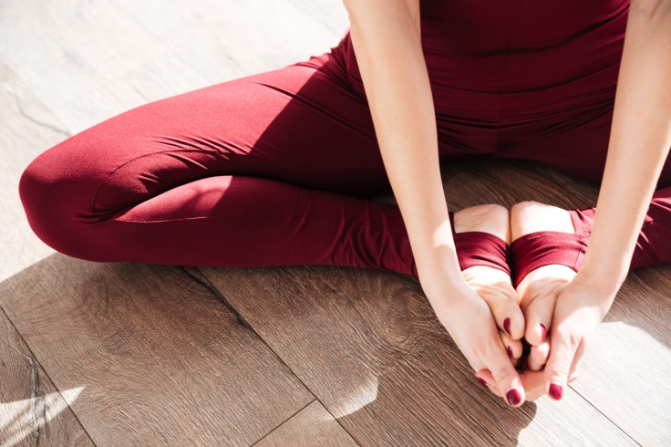 Hands and legs of young woman doing yoga barefoot